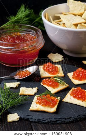 Canape with red caviar on slate plate over wooden table vertical selective focus