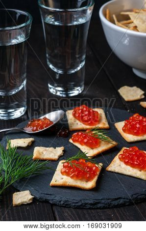 Biscuits salty crackers with red caviar and vodka on wooden table vertical selective focus