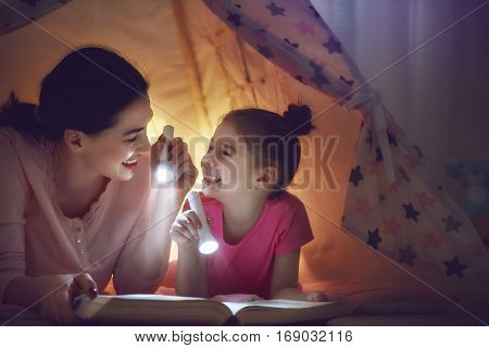 Family bedtime. Mom and child daughter are reading a book with flashlights in tent. Pretty young mother and lovely girl having fun in children room.
