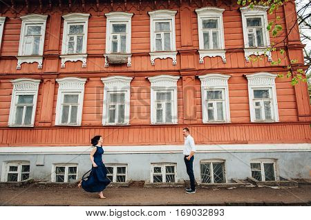 Young Couple Walking At Old Wooden House