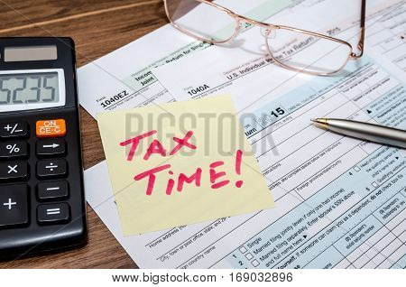 Tax Time Word On Tax Form With Calculator, Pen, Glasses