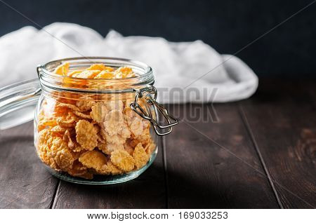 Close up of cornflackes in jar on dark wooden background selective focus. Space for text.