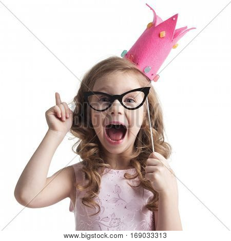Funny princess girl in pink dress and crown holding party glasses on stick and saying something smart with finger up