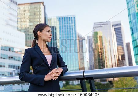Happy business woman portrait of young female urban professional businesswoman in suit standing outside office buildings cross-armed. Confident successful multicultural Chinese Asian / Caucasian woman