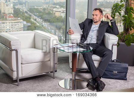 Businessman In Suit Looking At The Chart On The Sheet