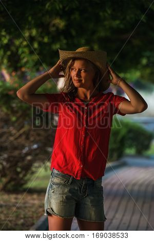 Young blond woman tourist in hat and red blouse standing in green alley and looking aside on summer day at sunset, Alanya, Mediterranean region, Turkey