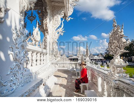 Happy beautiful woman in red shirt and hand in front of Wat Rong Khun The White Temple in Chiang Rai Thailand
