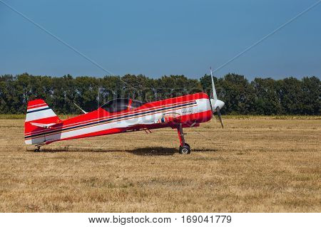 Small Red And White Private Plane With Propeller Stands At The Airport, In A Bright, Sunny Day.