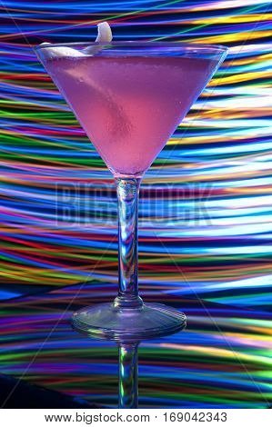 Colorful light painted cosmopolitan alcoholic beverage in glass reflections