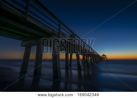 Beautiful golden orange sunset behind silhouetted public pier Naples, Florida