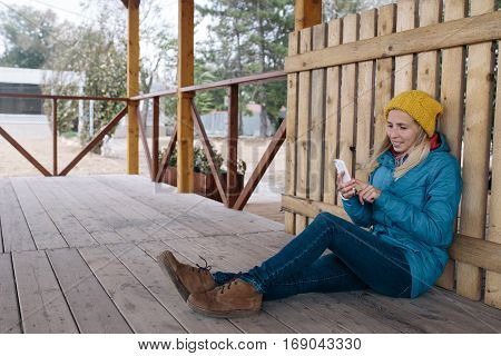 smiling young woman in yellow knitted hat and a blue jacket is sitting on a floor of wooden terrace and using smart phone