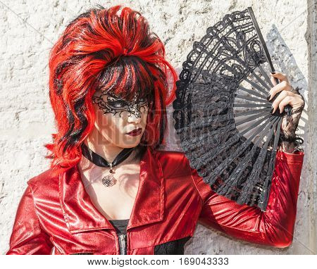 Venice Italy-February 18 2012:Portrait of a person wearing a red and black disguise with a fan posing near a stone wall during The Venice Carnival days.