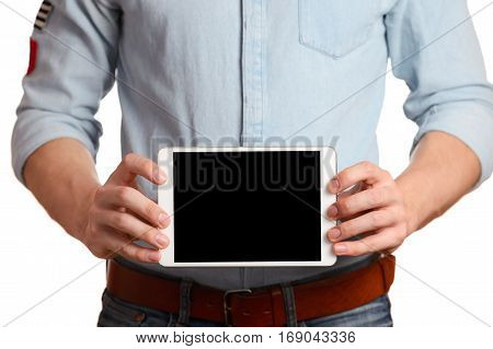 a man in a light blue shirt and jeans with a brown belt is holding tablet pc isolated on white background, pointing to the screen tablet PC, showing all right