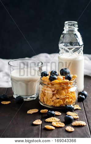 Cornflackes with blackberries and milk on dark wooden background selective focus vertical. Healthy food concept.
