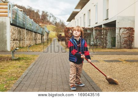 Cute little boy sweeping the backyard on a early spring day