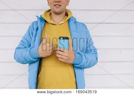young man in a blue jacket holding a mobile phone in one hand and the other showing a thumbs up on white wooden background