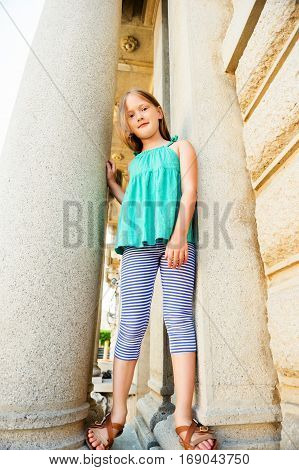 Summer portrait of a cute little girl wearing green top, plying outdoors in a city