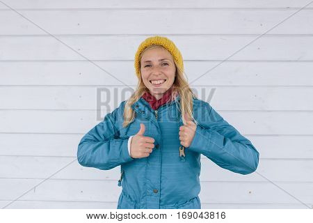 happy smiling woman in yellow knitted hat and a blue jacket showing thumbs up. happy people concept