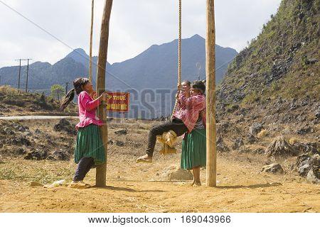 Ha Giang, Vietnam - Feb 7, 2014: Unidentified Hmong children playing swing game in playground in mountainous region