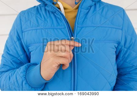 man buttons blue quilted jacket. cropped image of a man's hand fastens with a zipper on the jacket on a white background. close up