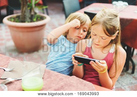 Two kids playing electronic games on the phone while waiting food orders in restaurant