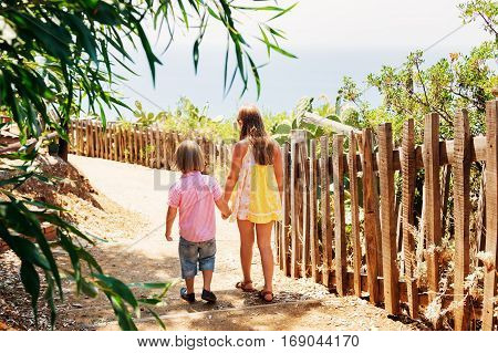 Two kids walking dowm the small path, back view, image taken in Capo Vaticano, Calabria, Italy