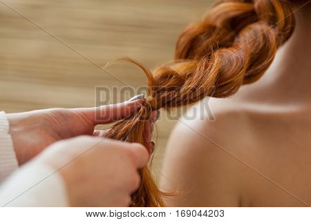 Beautiful, With Long, Red-haired Hairy Girl, Hairdresser Weaves A French Braid Close-up, In A Beauty