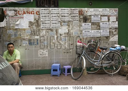 Hanoi, Vietnam - Mar 29, 2014: Old white wall with a lot of advertising papers sticking on it.