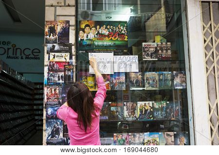 Hanoi, Vietnam - Mar 29, 2014: Unidentified woman tear off advertising paper showing new coming DVD
