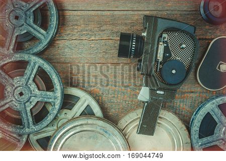 Old movie camera and film reel lying on a wooden table.Film effect from the illuminated edges