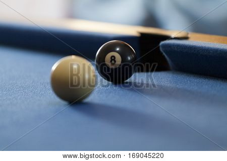White and black billiard balls in a pool table. Focus on black billiard ball