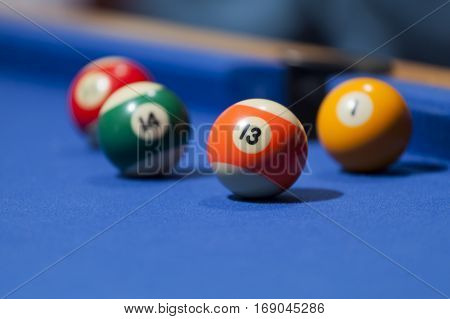 Orange, green, yellow and red billiard balls in a pool table. Focus on orange billiard ball