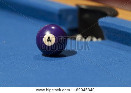 Purple billiard ball in a pool table. Focus on purple billiard ball