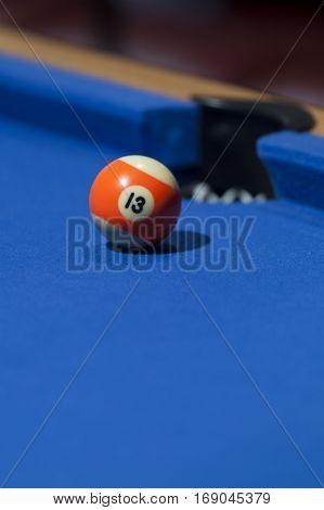 Orange billiard ball in a pool table. Focus on orange billiard ball