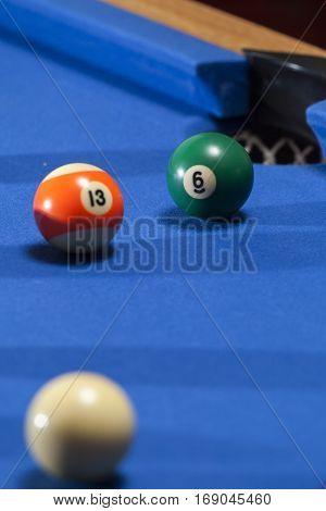 White, orange and green billiard balls in a pool table. Focus on green billiard ball