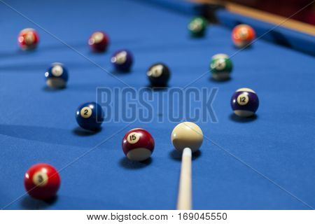 Billiard balls in a pool table with pool cue. Focus on white billiard ball