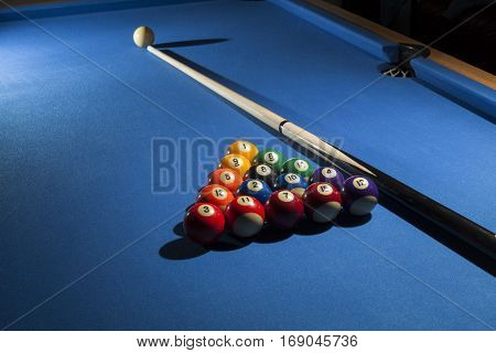 Pool billiard balls in commonly used starting position with pool cue . Focus on all billiard balls