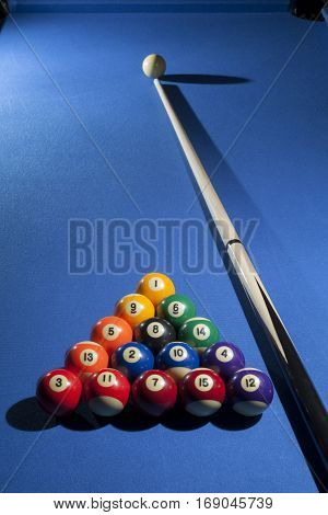 Pool billiard balls in commonly used starting position with pool cue.  Focus on all billiard balls
