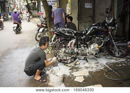 Hanoi, Vietnam - Apr 13, 2014: Unidentified man washes customer's motorbike on street in Hanoi, Vietnam
