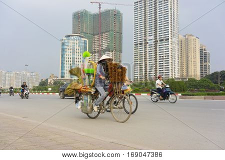 Hanoi, Vietnam - April 13, 2014: Traffic on Hanoi street with under construction buildings on background. Hanoi Capital region will be a large synthetic economic region of nation and Asia
