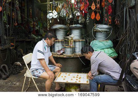 Hanoi, Vietnam - Apr 20, 2014: Unidentified men play chess in front of a tooling store on Hanoi street, Vietnam