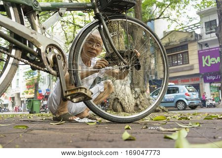 Hanoi, Vietnam - May 2, 2014: Unidentified old man fixing his bicycle on street side in Phan Dinh Phung str, Hanoi, Vietnam