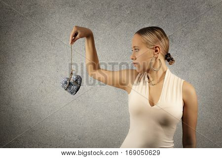 Beautiful young woman in casual cloths holding stone heart in jute bondage against grey texture wall background horizontal view