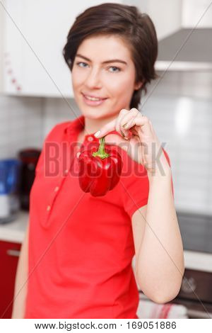 Photo of woman with pepper in kitchen