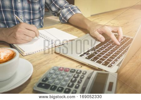 Business man using laptop computer with hand holding pen point notebook and coffee hot latte art. on wood desk. vitage tone.