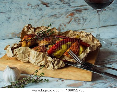 Chicken legs grilled on a wooden board with vegetables, garlic and thyme. Dinning concept