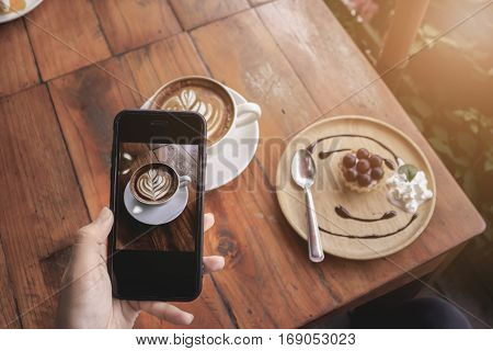 young girl hand holding smartphone for Photo of latte art coffee on camera display while shooting