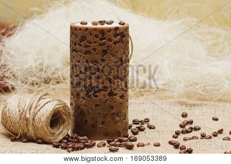 Beautiful Decorative Handmade Candle With Coffee Beans On Old Sackcloth Background.