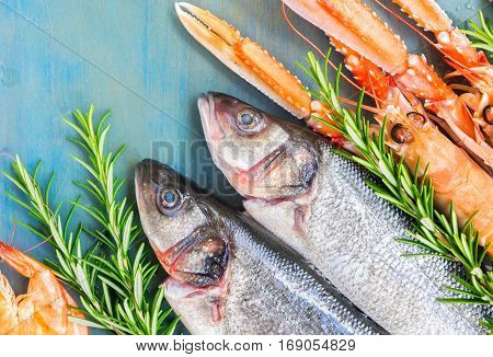 Fresh seafood and fish flat lay scene on blue background close up