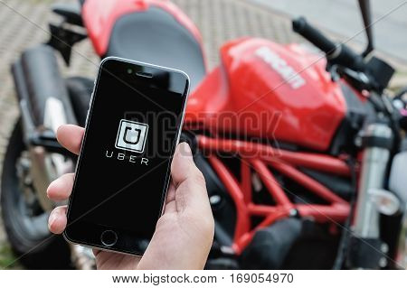 CHIANG MAITHAILAND - Aug 272016 : A MAN hand holding Uber app showing on iphone 6s with background Ducati motorcycle. Uber is smartphone app-based transportation network